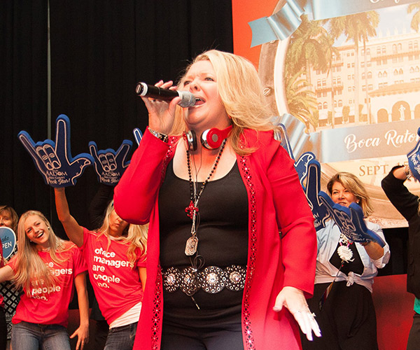 Lorie Streeter with a microphone singing on the stage